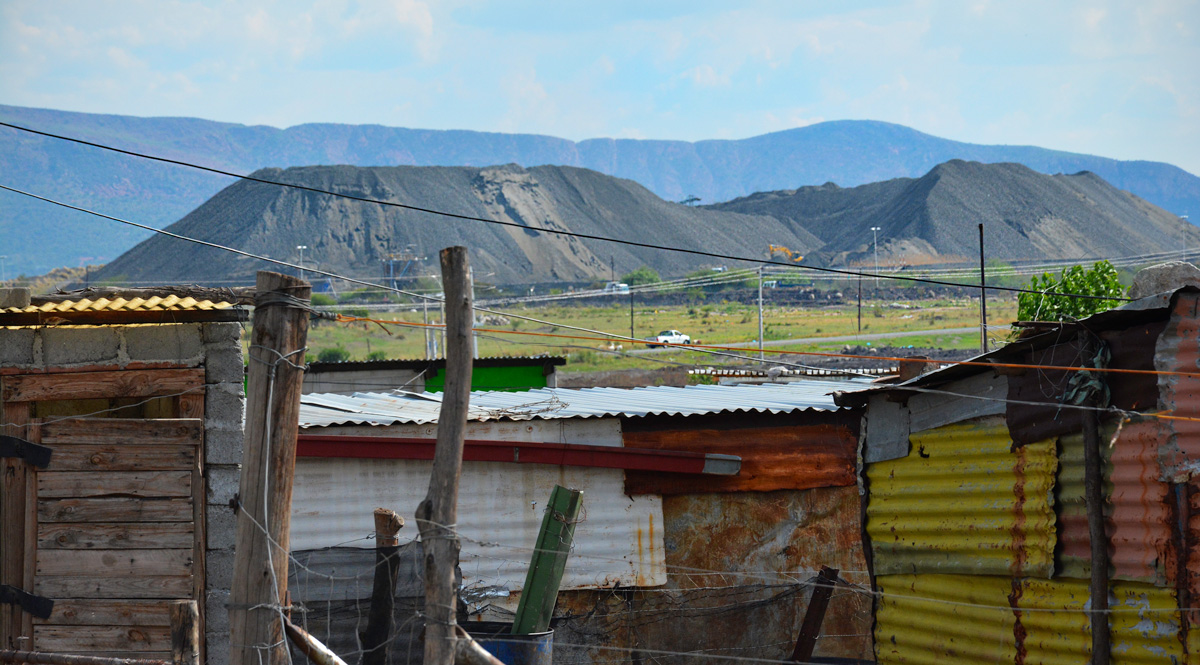 A platinum mine looms over a nearby settlement in South Africa