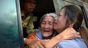 Cambodian land rights activist Nget Khun, known locally as 'Mommy', hugs her daughter through a window of a prison car at the Appeal Court in Phnom Penh in January this year