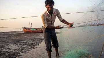 A fisherman near Mundra, India, prepares the net for the next day's fishing trip