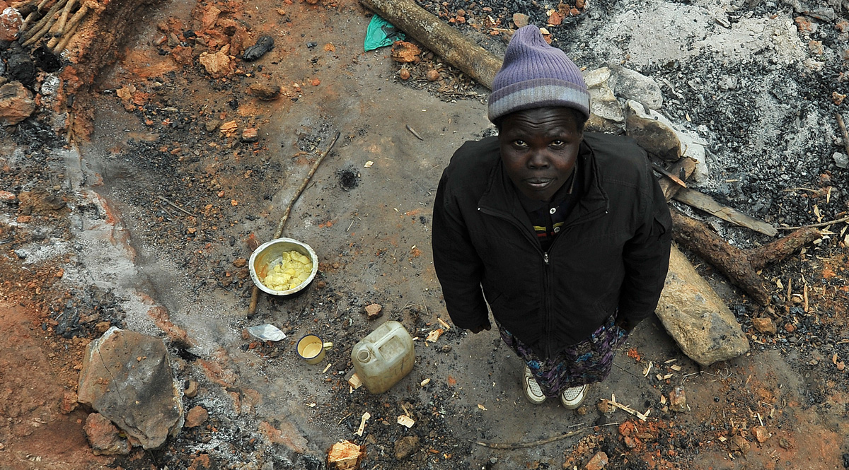 A woman stands in the remains of her home in Kenya, which she says was burned by the Kenya Forest Service, which has recieved World Bank funding