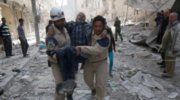 Emergency personnel carry an injured man following reported air strikes by government forces on Aleppo in March 2015