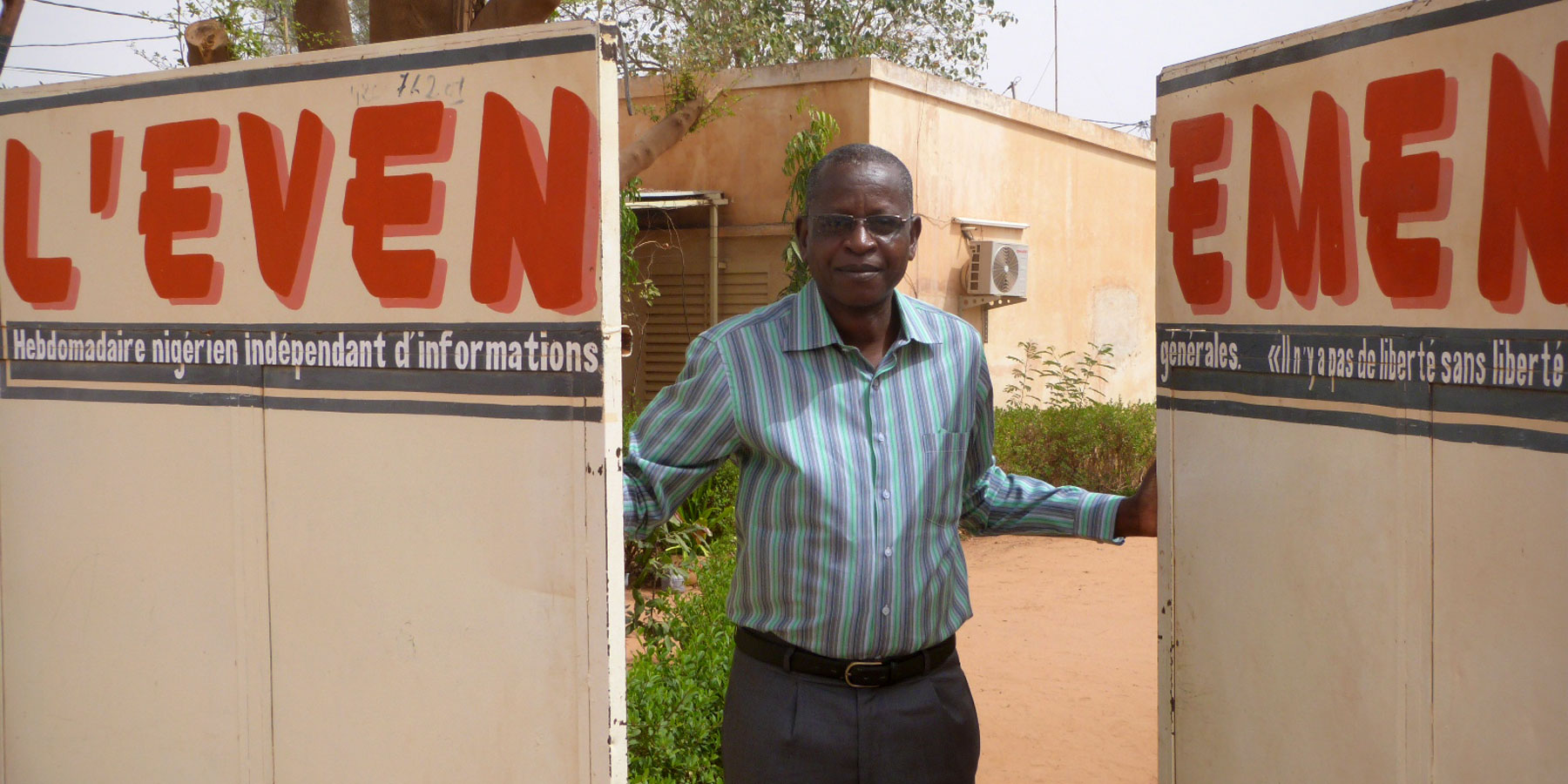 Journalist Moussa Aksar stands at the entrance to his newspaper, L'Evenement, in Niger