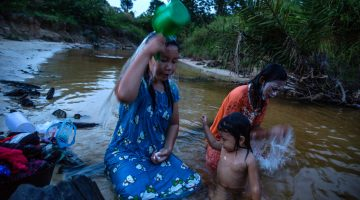 Locals bathe in the river next to the area where 35 homes were destroyed by police and personnel from Asiatic Persada in 2011