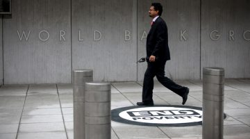 A man walks by the entrance to the World Bank Group headquarters in Washington, DC