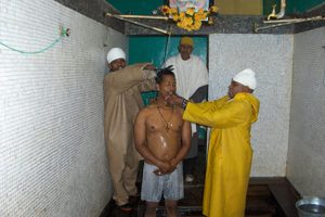 A man is showered in holy water as Atnafu Betseha, an Orthodox priest, imposes a large iron cross on him