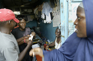 Marian Debo, second from left, from Medecins Sans Frontieres (MSF), distributes condoms at a shop in Lagos