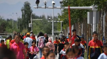 schoolchildren walking below surveillance cameras in Akto, south of Kashgar, in China's western Xinjiang region