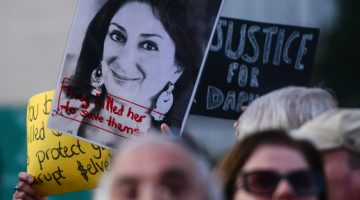 Protesters hold Daphne Caruana Galizia signs in Malta