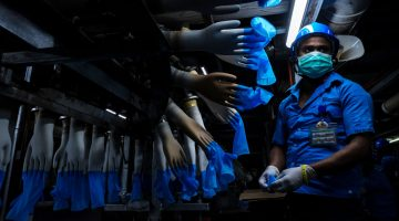 An employee monitors latex gloves on hand-shaped molds moving along an automated production line at a Top Glove Corp. factory in Malaysia