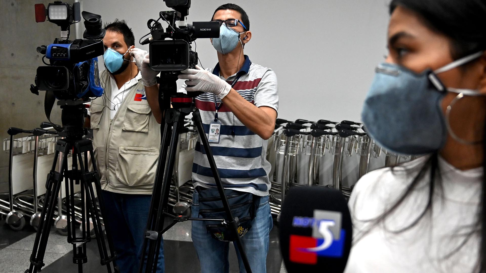 Journalists in Colombia wear protective face masks