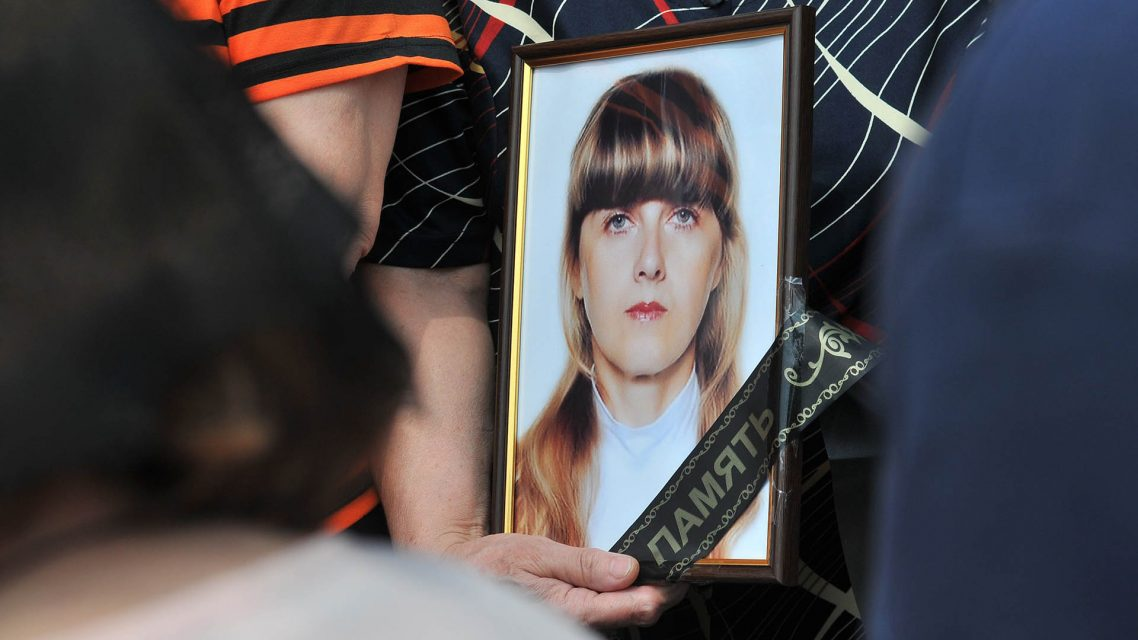 Relatives hold Nadezhda Kulinich's portrait during a funeral
